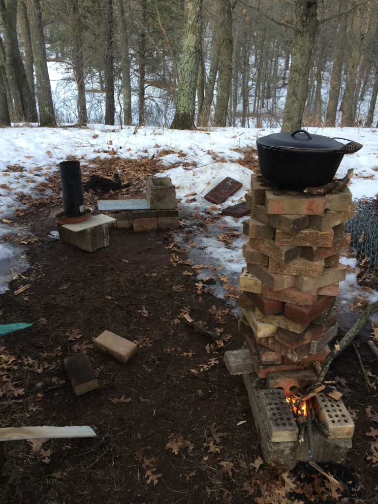 rocket stove 1.0 in action with 2.0 being built in the background