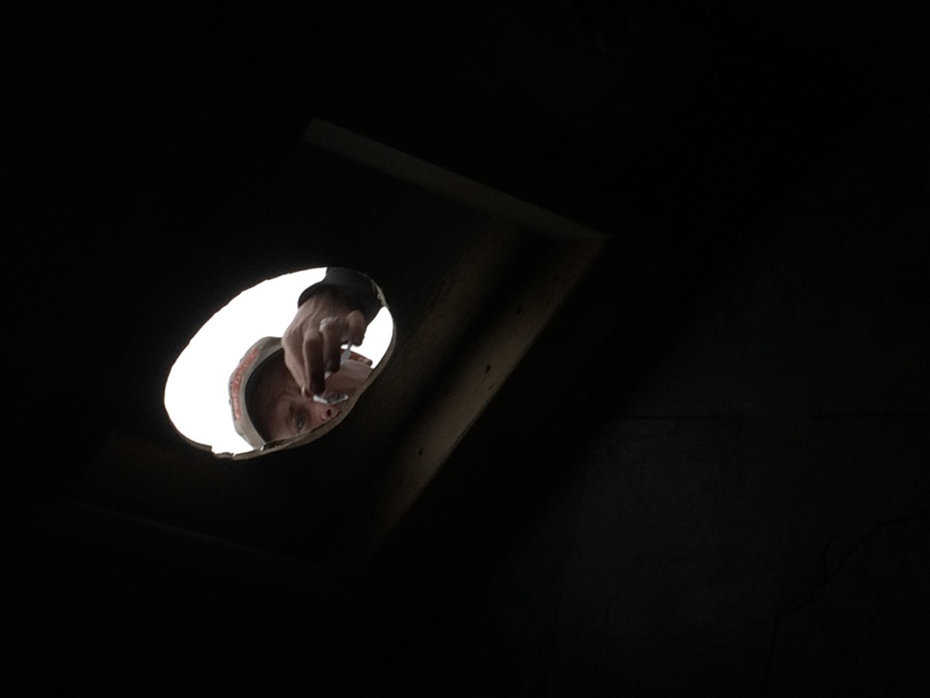 Shane peers through the new hole in his home's roof, in the midst of the wood stove installation (oops this pic is actually from the last days of December)