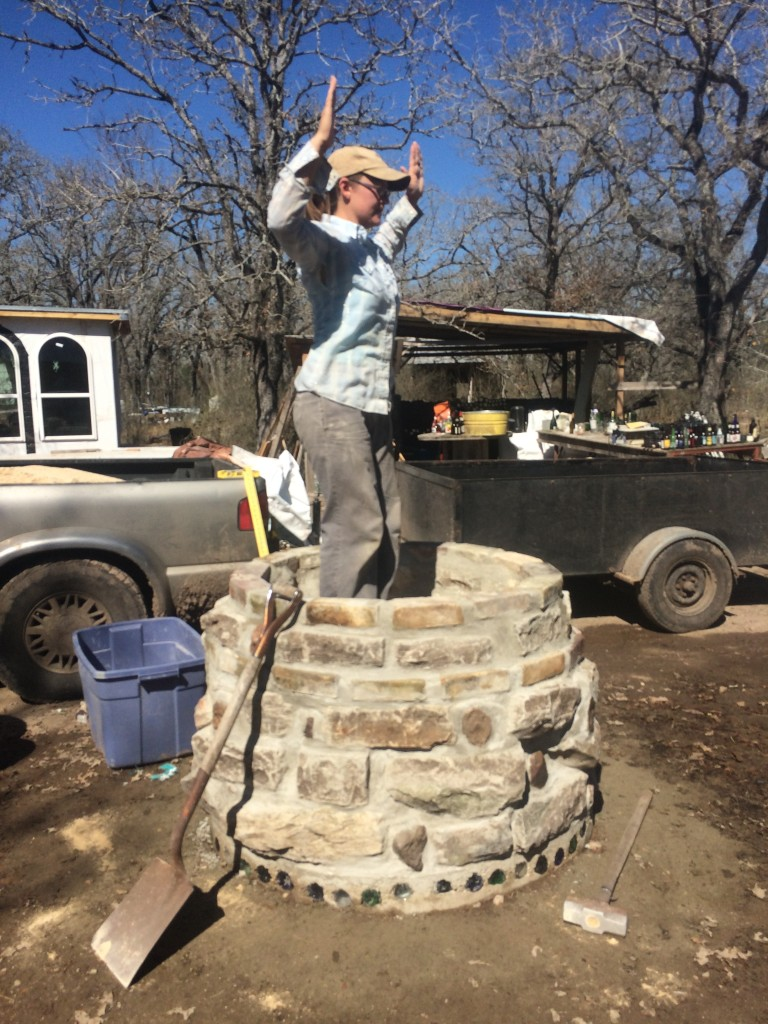 Kristin does the Tamping Dance - we filled the lower base with a mix of sand and crushed glass (necks left over from bottle bricks used in the ongoing bottle-house construction, visible in the background)