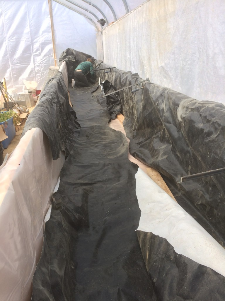 Kristin gluing together scraps of tarp to line the new raised grow bed that Kristin and Dee built before I got there