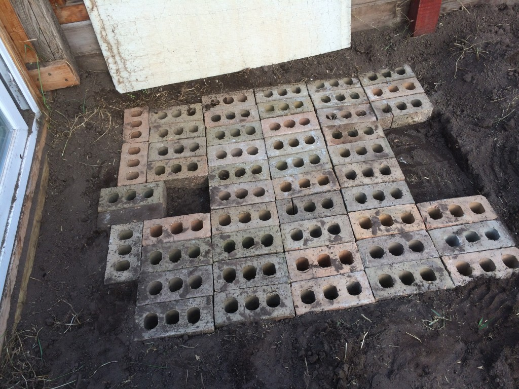 creating the subsurface foundation for the combustion chamber - the air spaces in the bricks add insulation to keep heat where it's wanted - not absorbing into the ground
