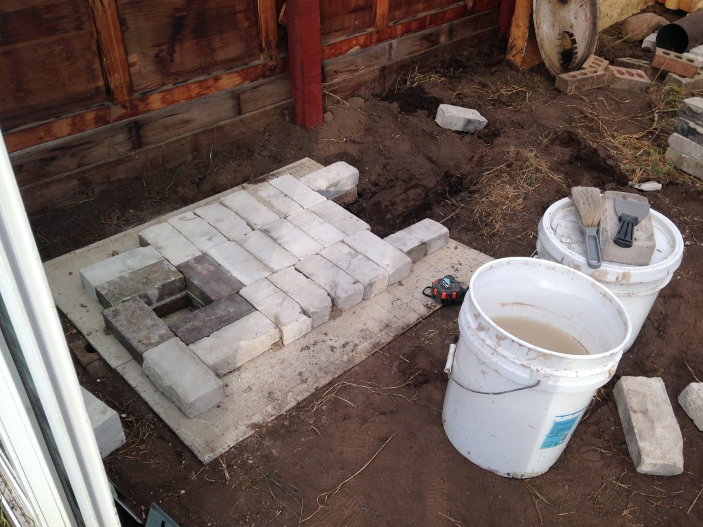 laying the base layer, with pits for ash cleanouts. White bricks insulate against heat loss, keeping temperatures high for the heat riser, where even the smoke will burn up