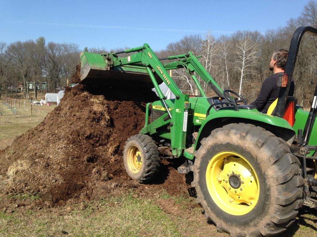 turning the pile of old horse manure with Neighbor Dave's tractor