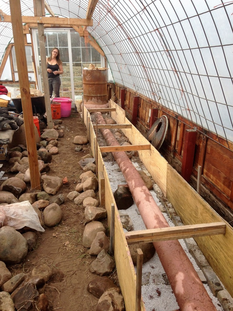 slowly filling the forms with clay/sand mix and rocks. Kristin down at her mixing station.