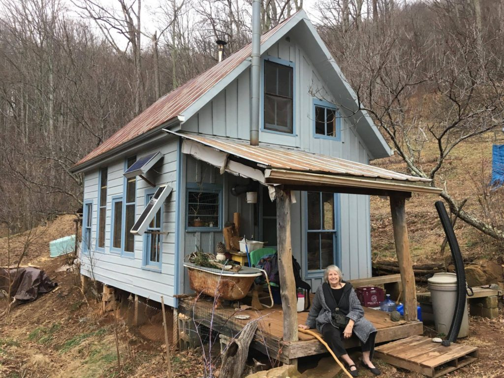 Jacqueline in front of Pat's off-grid homestead