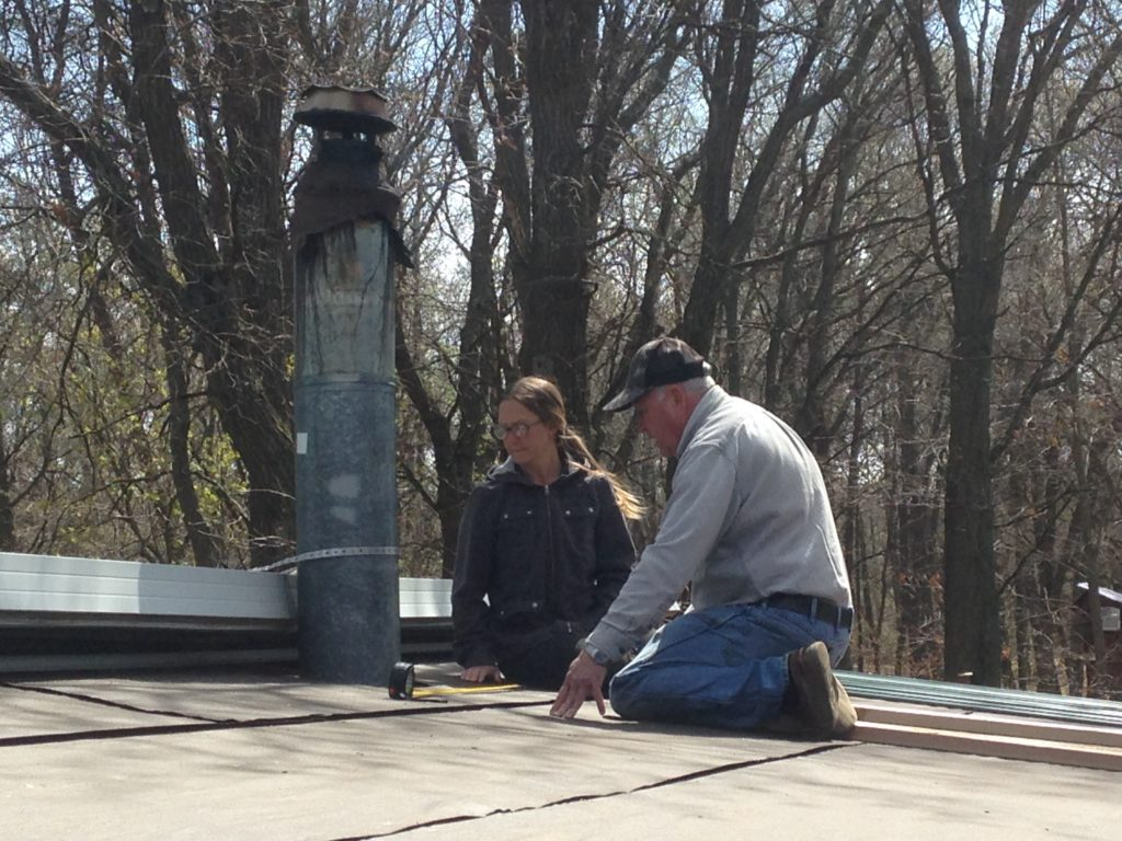 Kristin and her dad working on the screen porch roof