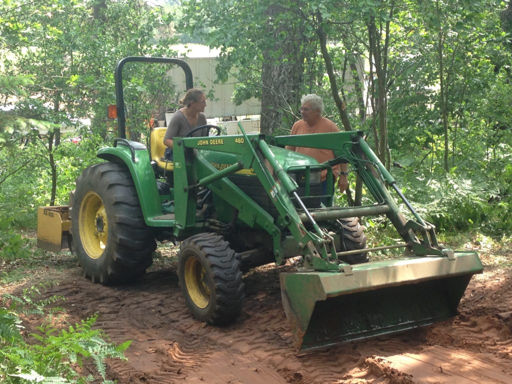Neighbor Dave teaching Kristin how to dig a root cellar hole with his tractor