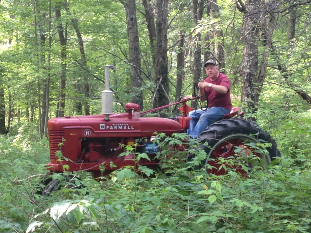 Jim pilots his tractor through the woods