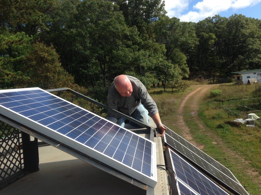 Kristin's dad Jim helping install the solar panels, using a frame he and his son Joe welded for us
