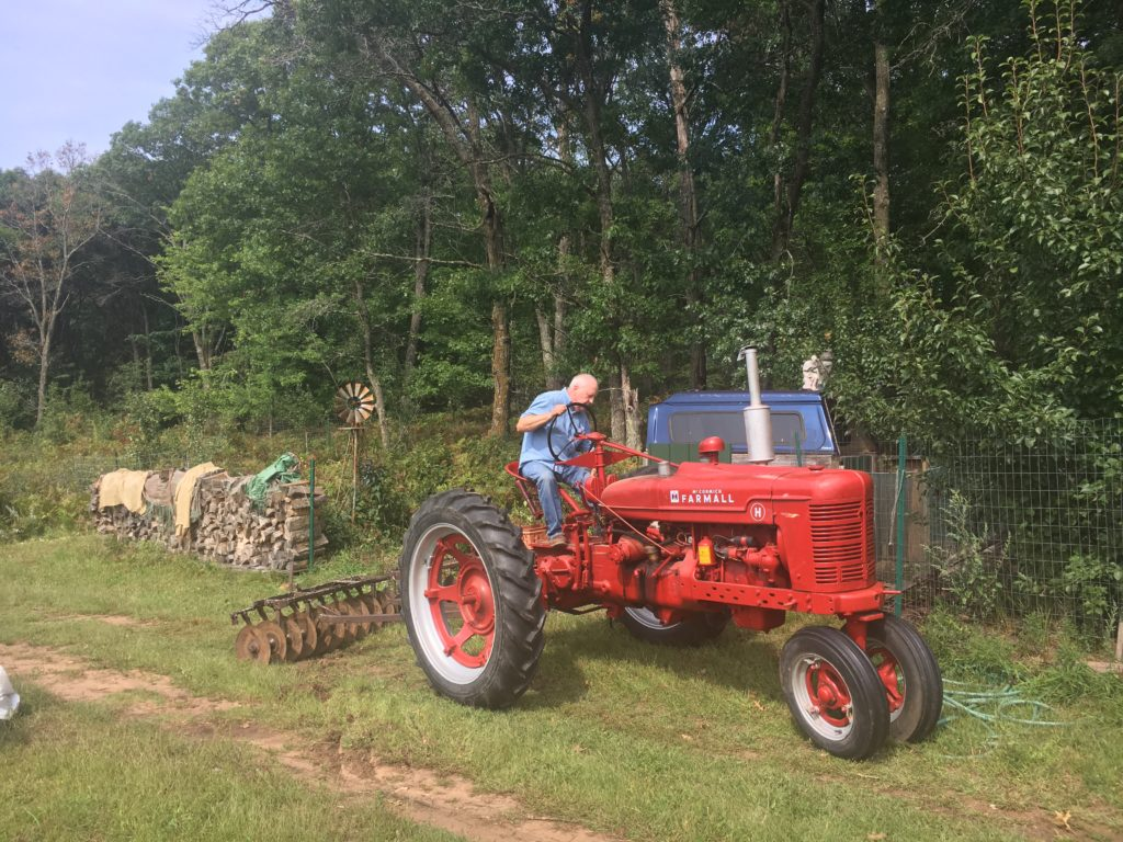 Grandpa Jim moves some of the old implements out of the pear tree patch